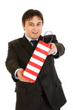 Smiling young businessman giving shopping bag Royalty Free Stock Photo