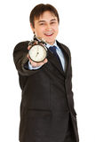 Smiling young businessman holding alarm clock Stock Photo