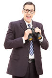 Smiling young businessman holding binoculars Royalty Free Stock Photos