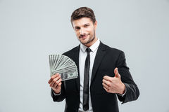 Smiling young businessman holding money and showing thumbs up Royalty Free Stock Images