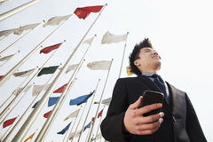 Smiling young businessman holding a phone with flags in the background Royalty Free Stock Images
