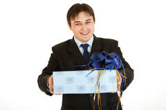 Smiling young businessman holding present in hands Stock Photos