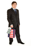 Smiling young businessman holding shopping bags Royalty Free Stock Image
