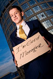 Smiling young businessman holding sign Royalty Free Stock Images