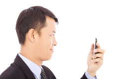 Smiling young businessman holding a smartphone and watching Stock Image