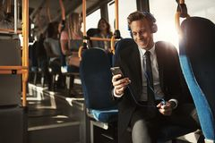 Smiling young businessman listening to music on his morning comm stock photography