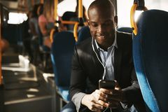 Smiling Young Businessman Listening To Music On His Morning Comm Stock Photo