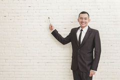 Smiling young businessman looking at camera while pointing at co Royalty Free Stock Photo