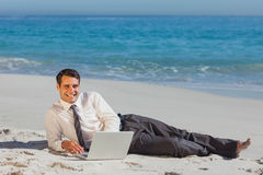 Smiling young businessman lying on the sand with his laptop Stock Images