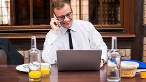 Smiling young businessman making a call with his smartphone in a restaurant. Stock Photo