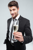 Smiling young businessman making cheers with glass of champagne Royalty Free Stock Image