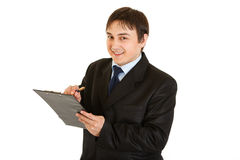 Smiling young businessman making notes in document Stock Images