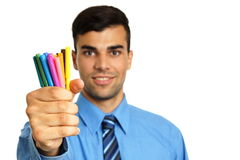 Smiling young businessman with markers. Smiling young businessman in blue shirt shows you colored markers, focus is on markers, right you can write some text royalty free stock photography