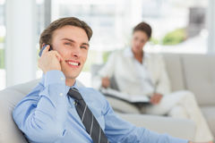 Smiling young businessman on the phone sitting on couch. In the office Royalty Free Stock Images