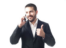Smiling young businessman on the phone with thumbs up. Royalty Free Stock Photo