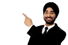 Smiling young businessman pointing away Royalty Free Stock Image