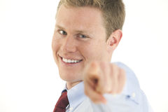 Smiling young businessman pointing finger at camer Stock Photography