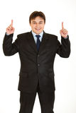 Smiling young businessman pointing up isolated Royalty Free Stock Image