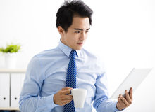 Smiling young businessman reading the tablet Royalty Free Stock Image