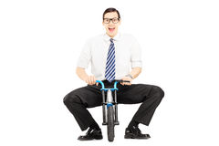 Smiling young businessman riding a small bicycle royalty free stock photography