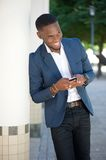 Smiling young businessman sending text message by cellphone Royalty Free Stock Image