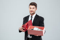 Smiling young businessman showing present box full of money Royalty Free Stock Image