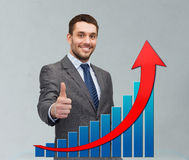 Smiling young businessman showing thumbs up. Business, people, economics, success  and gesture concept - smiling young businessman showing thumbs up over gray Stock Photo