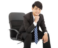 Smiling Young businessman sitting on a chair. In studio Royalty Free Stock Photo