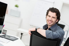Smiling young businessman sitting in his office Royalty Free Stock Image