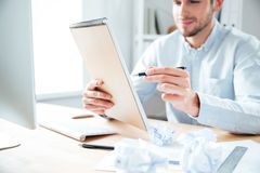 Smiling young businessman sitting and writing in notepad at workplace Stock Photos