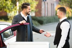 Young Businessman Giving Car Key To Valet. Smiling Young Businessman Standing Beside Car Giving Key To Valet stock photo