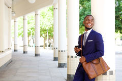 Smiling young businessman standing with cell phone outdoors Royalty Free Stock Image