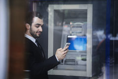Smiling young businessman standing in front of an ATM and looking at his phone Stock Photos