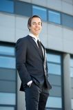 Smiling young businessman standing outdoors Royalty Free Stock Image