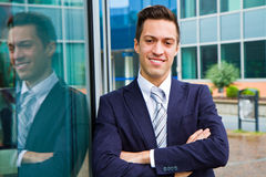 Smiling young businessman standing outside a building Stock Photo