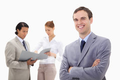Smiling young businessman with talking colleagues behind him Royalty Free Stock Photos