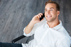 Smiling young businessman talking on mobile phone in office Stock Photography