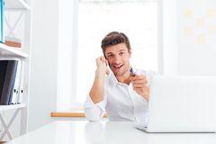 Smiling young businessman talking on mobile phone and pointing pen Stock Photos