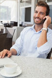 Smiling young businessman talking on phone using his laptop. In patio of restaurant Royalty Free Stock Photography
