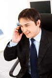 Smiling young businessman talking on telephone. Smiling young business man talking on telephone in office Royalty Free Stock Image