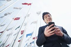 Smiling young businessman texting on his phone outdoors with flags in the background royalty free stock photos