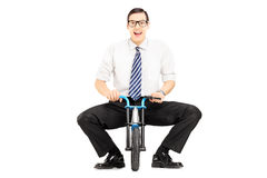 Smiling young businessman with tie on a small bicycle Stock Photos
