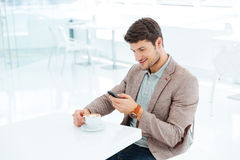 Smiling young businessman typing message on smartphone while sitting Stock Photography