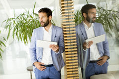 Smiling young businessman using his digital tablet at the office Royalty Free Stock Photo
