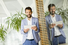 Smiling young businessman using his digital tablet at the office Royalty Free Stock Photos