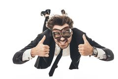 smiling young businessman in vintage aviation goggles falling and showing thumbs up royalty free stock photos