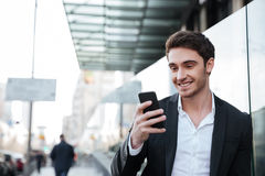 Smiling young businessman walking near business center. Image of smiling young businessman walking near business center. Chatting by phone. Looking aside Royalty Free Stock Photo