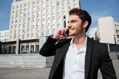 Smiling young businessman walking outdoors. Royalty Free Stock Photos