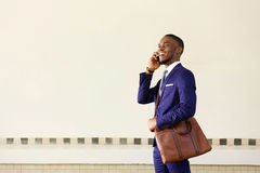 Smiling young businessman walking and talking on mobile phone Stock Images