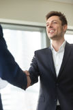 Smiling young businessman wearing black suit shaking male hand, Stock Image